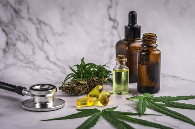 Assorted cannabis products, pills and cbd oil over medical presc