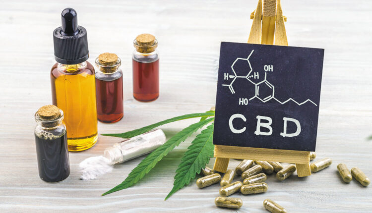Full spectrum Cannabidiol CBD oils, capsules and crystals isolate with small blackboard with CBD word and chemical structure